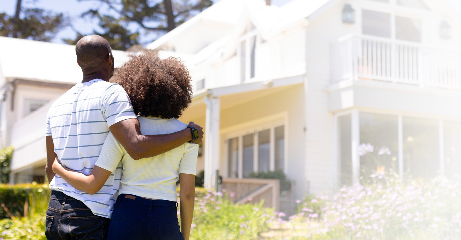 Young couple with their arms around each other looking at their dream home